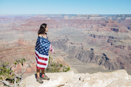 USA, Arizona, woman wrapped in American flag enjoying view of Grand Canyon National Park - GEMF02178