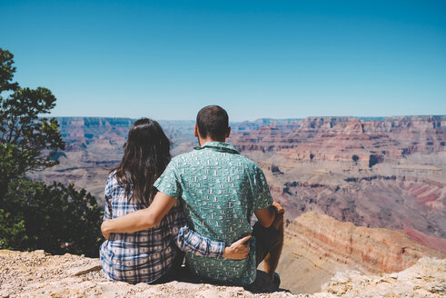 USA, Arizona, Grand Canyon National Park, back view of couple sitting side by side looking at view - GEMF02199
