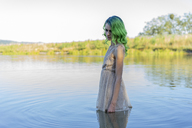 Young woman with dyed green hair standing dressed in water of lake - AFVF00998