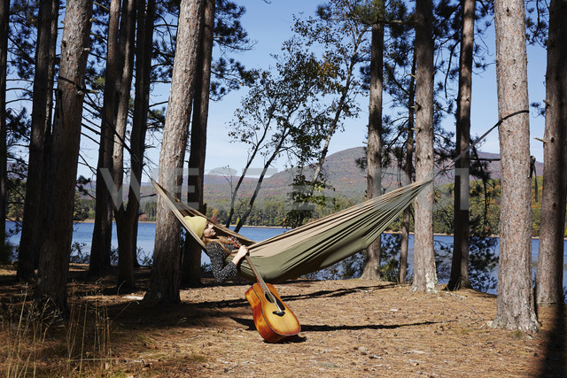 A woman lying in a hammock relaxing, under the pine trees by a lake. - MINF01039