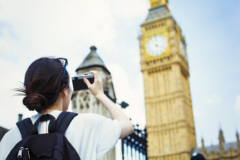 Young Japanese woman enjoying a day out in London, taking a picture of Big Ben. - MINF01084