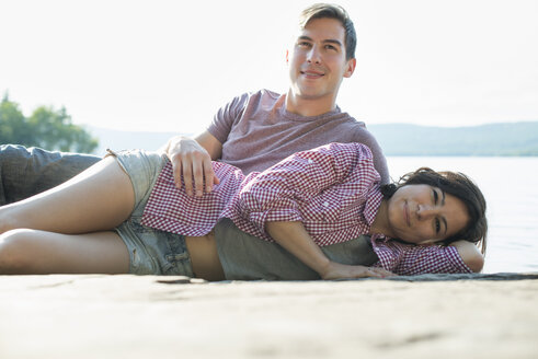 A couple relaxing, lying on a wooden jetty by a lake in summer. - MINF01249