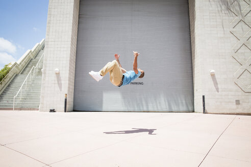 Young man somersaulting in front of a garage door. - MINF01375