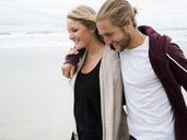 Young man and young woman walking on a beach, smiling. - MINF01384