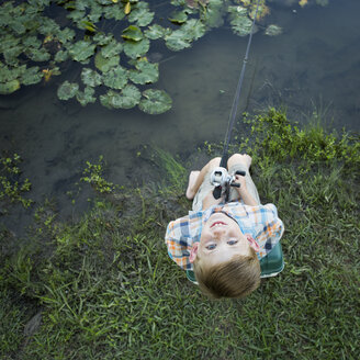 A young boy outdoors, standing on a riverbank looking up above his head. - MINF01528