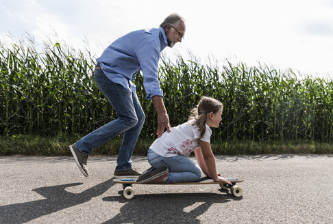 Mature man helping little girl to learn skateboarding - UUF14561