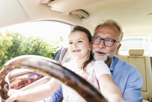 Little girl sitting on lap of grandfather, pretending to steer the car - UUF14567