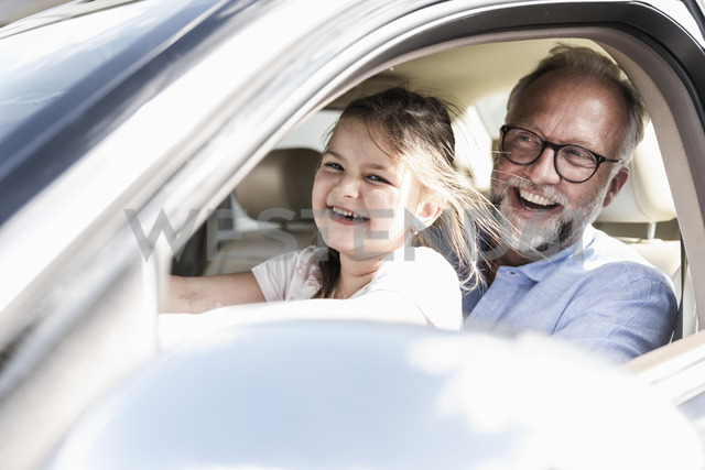 Little girl sitting on lap of grandfather, pretending to steer the car - UUF14570