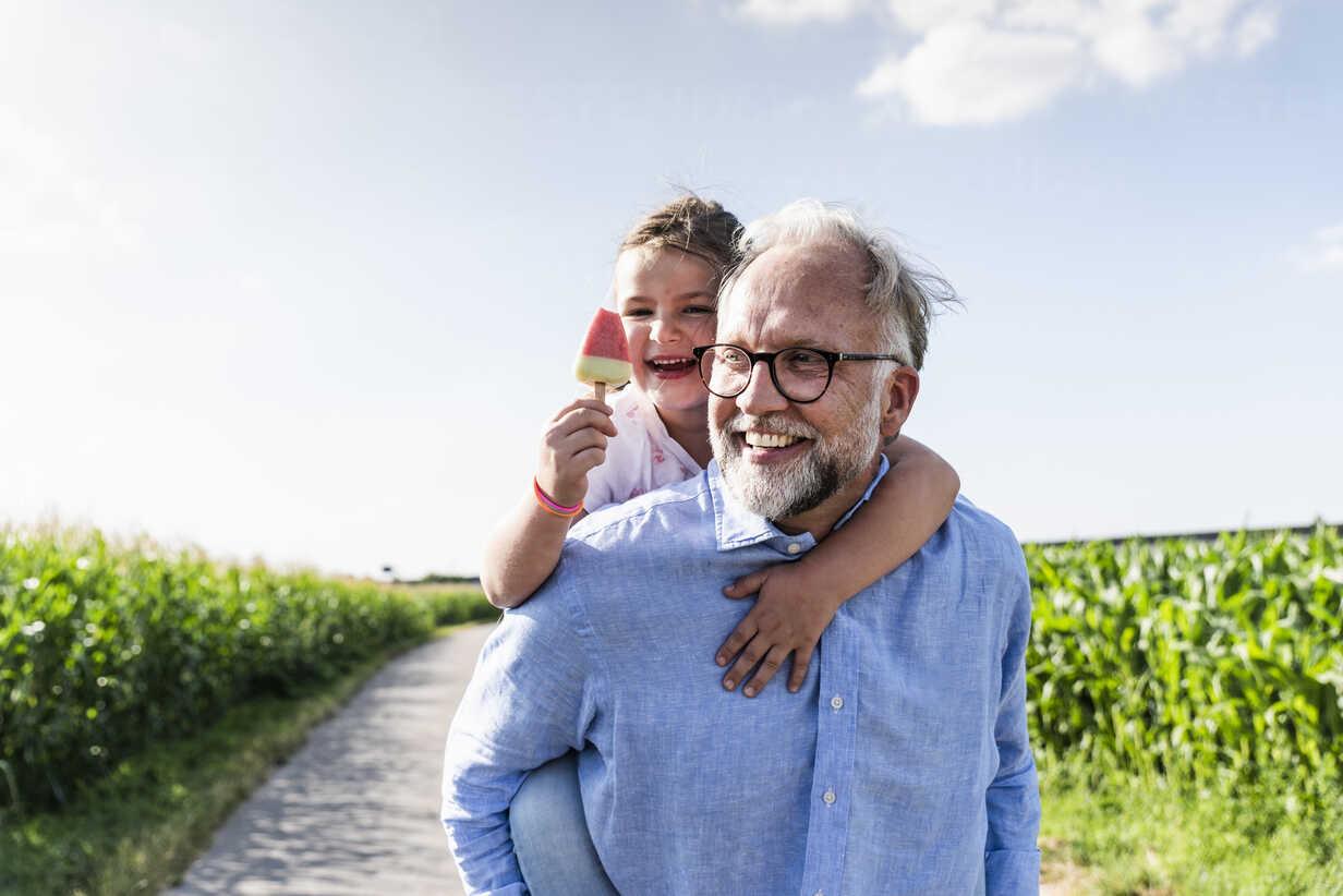Grandfather carrying granddaughter piggyback - UUF14579 - Uwe Umstätter/Westend61
