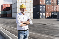 Businessman at cargo harbour, wearing safety helmet, arms crossed - UUF14585