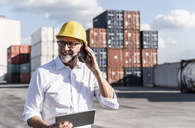 Businessman at cargo harbour, wearing safety helmet, using smartphone and digital tablet - UUF14591