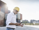 Businessman at cargo harbour, wearing safety helmet, using smartphone and digital tablet - UUF14594