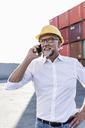 Businessman at cargo harbour, wearing safety helmet, using smartphone - UUF14606