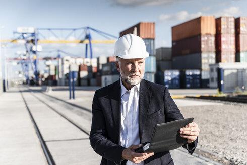 Businessman at cargo harbour, wearing safety helmet, using smartphone - UUF14609