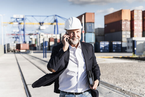 Businessman at cargo harbour, wearing safety helmet, using smartphone - UUF14612