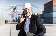Businessman at cargo harbour, wearing safety helmet, using smartphone - UUF14615