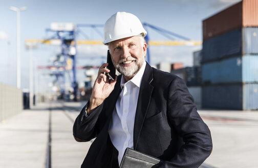 Businessman at cargo harbour, wearing safety helmet, using smartphone - UUF14615