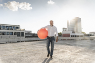 Mature man playing with orange fitness ball on rooftop of a high-rise building - UUF14630