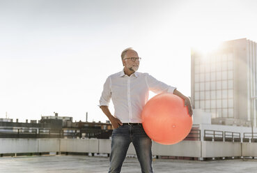 Mature man playing with orange fitness ball on rooftop of a high-rise building - UUF14633