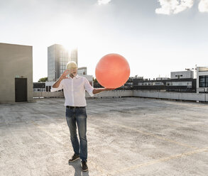 Mature man playing with orange fitness ball on rooftop of a high-rise building - UUF14636