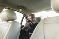 Mature businessman sitting on backseat in car, talking on the phone - UUF14639