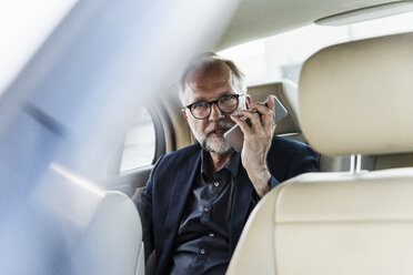 Mature businessman sitting on backseat in car, talking on the phone - UUF14648