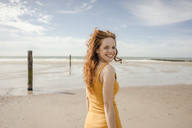 Portrait of a redheaded woman, laughing happily on the beach - KNSF04215