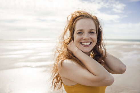 Portrait of a redheaded woman, laughing happily on the beach - KNSF04218