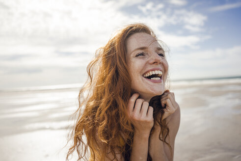 Portrait of a redheaded woman, laughing happily on the beach - KNSF04221