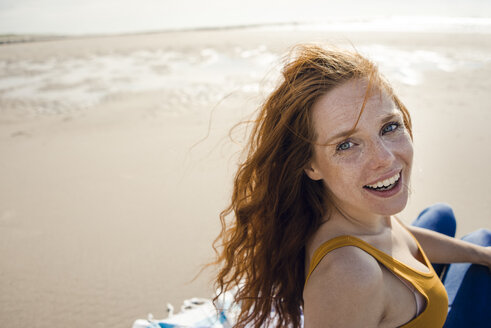 Portrait of a redheaded woman, laughing happily on the beach - KNSF04227