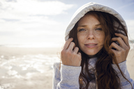 Woman wearing hood on a windy beach - KNSF04230