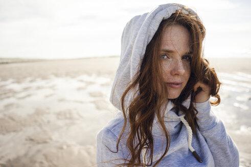 Woman wearing hood on a windy beach - KNSF04233