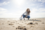 Woman with soccer ball crouching on the beach, looking away - KNSF04239