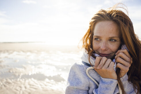 Redheaded woman enjoying fresh air at the beach - KNSF04242