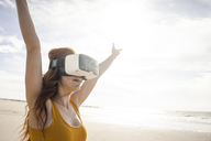 Redheaded woman using VR glasses on the beach - KNSF04254