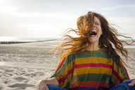 Woman sitting on the beach, screaming for joy - KNSF04260