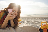 Redheaded woman lying on the beach with beach toys - KNSF04263