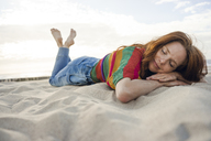 Redheaded woman lying in sand on the beach, with eyes closed - KNSF04266