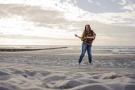 Happy woman having fun at the beach, dancing in the sand - KNSF04269