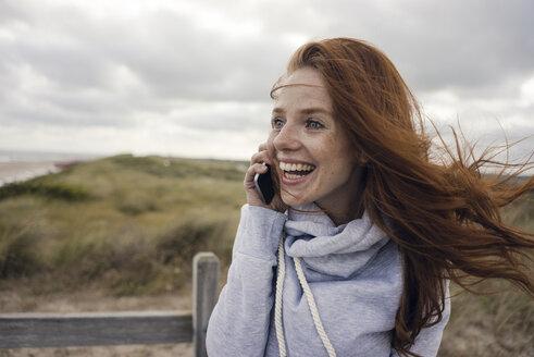 Redheaded woman using smartphone on the beach - KNSF04281