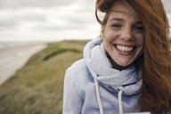 Redheaded woman enjoying fresh air at the beach - KNSF04284