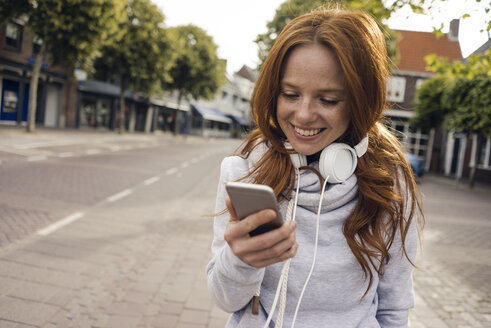 Redheaded woman using headphones and smartphone in the city - KNSF04287