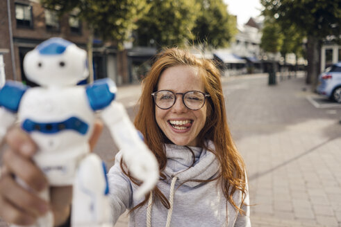 Redheaded woman showing toy robot - KNSF04290