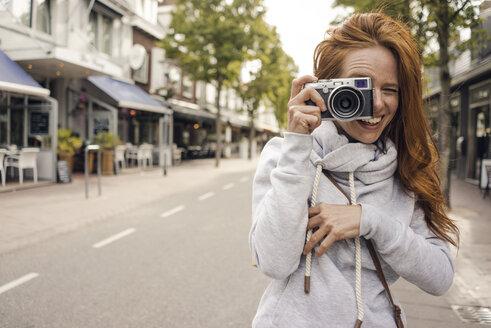 Redheaded woman using analogue camera - KNSF04293