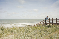 Woman sitting on fence at the beach, relaxing at the sea - KNSF04296