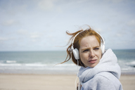 Redheaded woman relaxing at the beach, listening music with headphones - KNSF04299