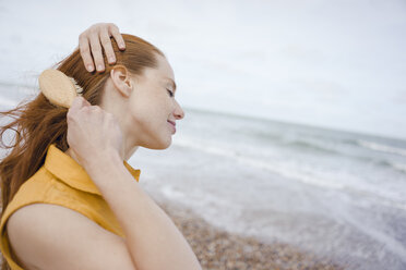 Woman using hair brush at the sea - KNSF04305