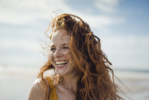 Portrait of a redheaded woman, laughing happily on the beach - KNSF04311