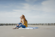 Woman sitting on the beach, enjoying the sun - KNSF04314