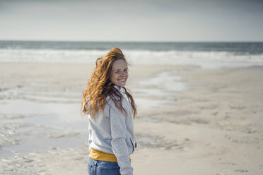 Redheaded woman relaxing on the beach, laughing - KNSF04320